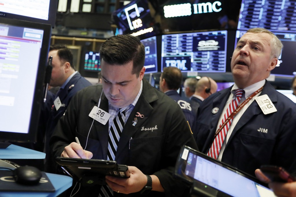 FILE- In this Feb. 5, 2019, file photo traders Joseph Lawler, left, and James Lamb work on the floor of the New York Stock Exchange. The U.S. stock ma