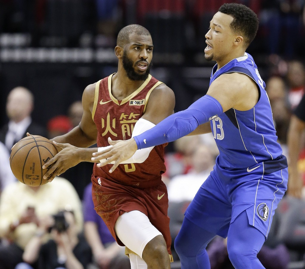 Houston Rockets guard Chris Paul, left, looks to pass as Dallas Mavericks guard Jalen Brunson applies defensive pressure during the first half of an N