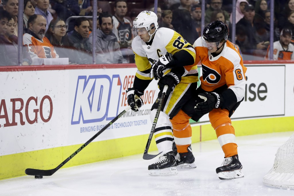 Pittsburgh Penguins' Sidney Crosby (87) and Philadelphia Flyers' Travis Sanheim (6) battle for the puck during the first period of an NHL hockey game,...