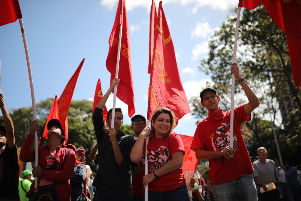 Members of Venezuela's Communist Youth hold red flags during a pro-government demonstration in Caracas, Venezuela, Tuesday, Feb. 12, 2019. Nearly thre...