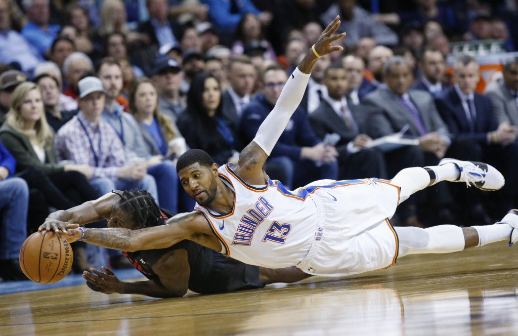 Oklahoma City Thunder forward Paul George (13) dives for the ball with Portland Trail Blazers forward Al-Farouq Aminu, left, in the second half of an