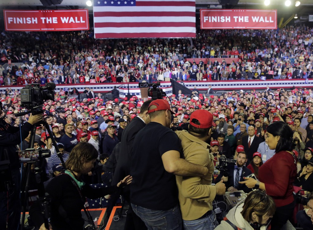 A man is restrained after he began shoving members of the media during a rally for President Donald Trump at the El Paso County Coliseum, Monday, Feb....