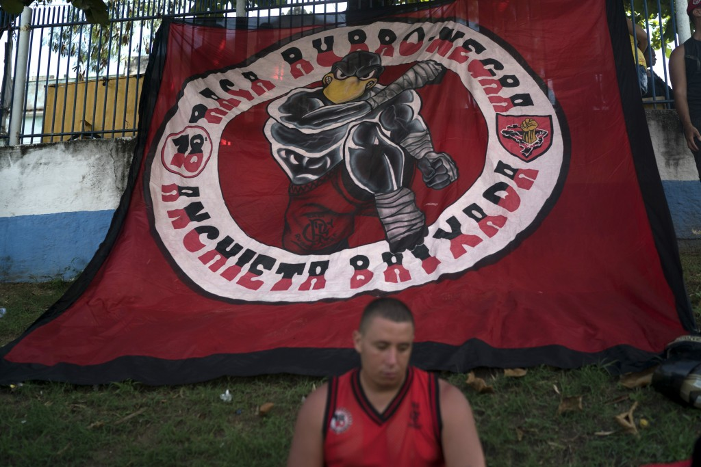 A soccer fan sits in front a giant banner depicting a vulture, the Flamengo's mascot, during the funeral of Samuel de Souza Rosa, one of the 10 young
