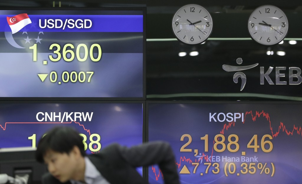 A currency trader watches the computer monitors near the screens showing the Korea Composite Stock Price Index (KOSPI), right, and the foreign exchang...