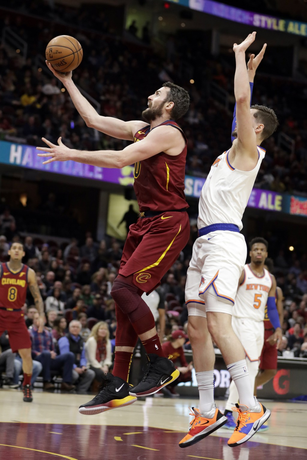 Cleveland Cavaliers' Kevin Love, left, drives to the basket against New York Knicks' Mario Hezonja, from Croatia, in the first half of an NBA basketba...