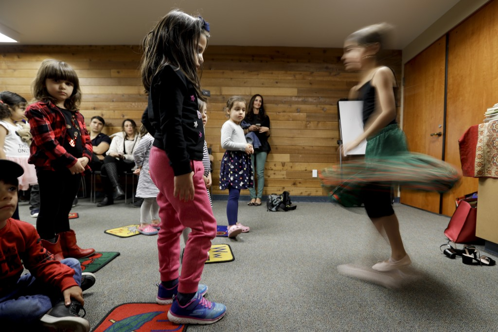 In this Wednesday, Jan. 23, 2019 photo, children dance during Persian story time at Irvine public library in Irvine, Calif. It's been four decades sin...
