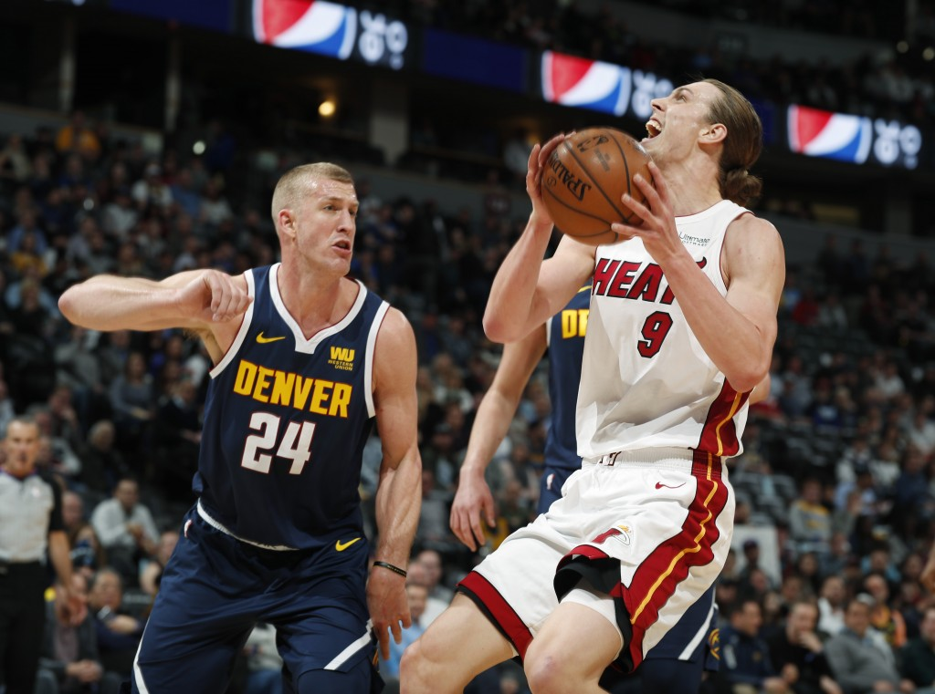 Miami Heat forward Kelly Olynyk, right, goes up for a basket as Denver Nuggets forward Mason Plumlee defends in the first half of an NBA basketball ga...