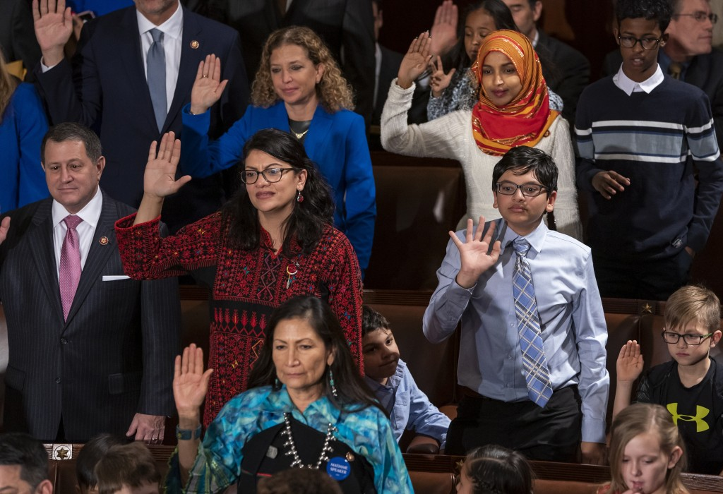 FILE - In this Jan. 3, 2019 file photo, Rep. Rashida Tlaib, D-Mich., center left, wears a Palestinian thobe as Democratic members of the House of Repr...