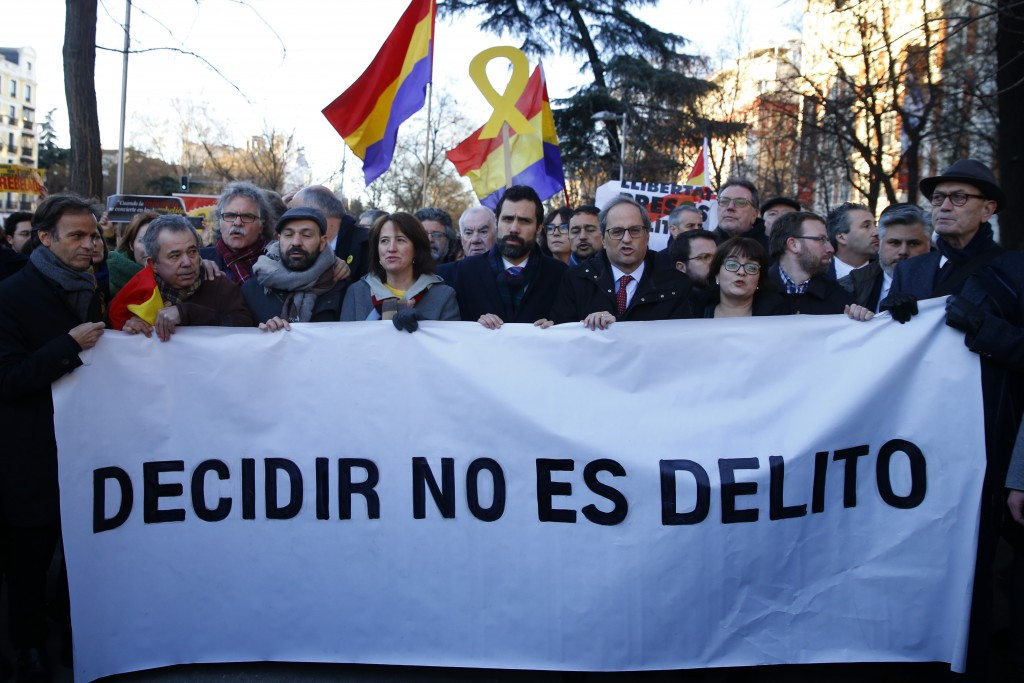 The president of Catalonian Parliament, Roger Torrent, center, and the Catalan regional President Quim Torra, center right, hold a placard that reads ...