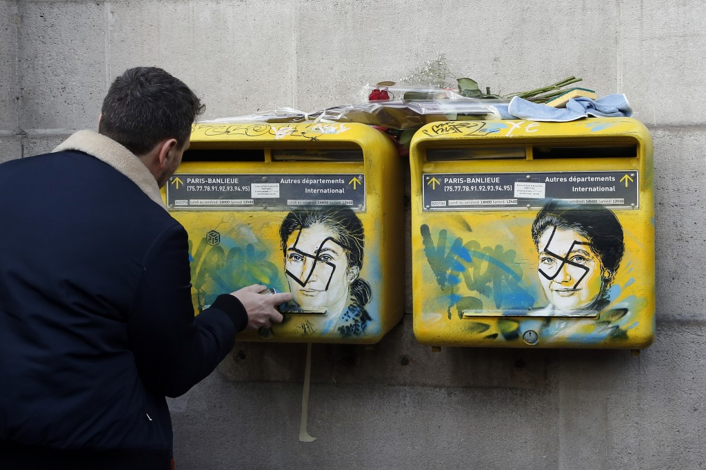 French street artist Christian Guemy, known as C215, cleans the vandalized mailboxes with swastikas covering the face of the late Holocaust survivor a