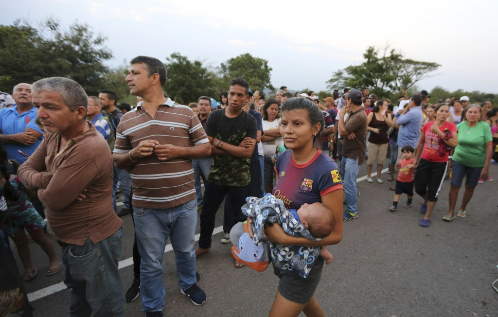 People line up to receive a bag with food subsidized by the Nicolas Maduro's government near the international bridge of Tienditas on the outskirts of