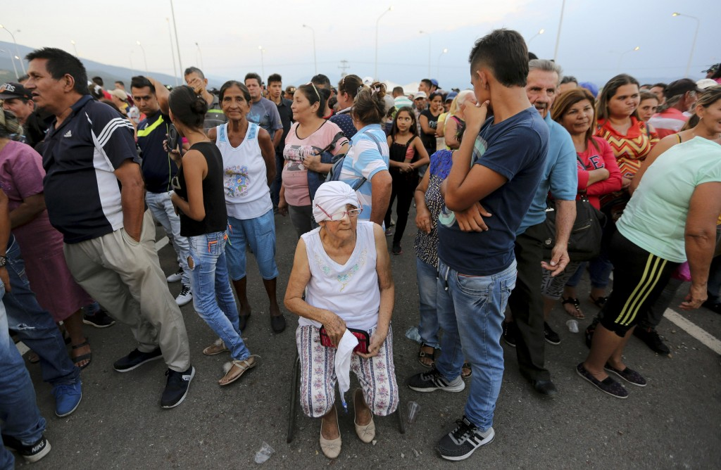 People line up to receive bags with food subsidized by the Nicolas Maduro's government near the international bridge of Tienditas on the outskirts of ...