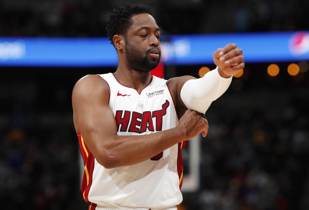 Miami Heat guard Dwyane Wade adjusts his sleeve as he takes the court against the Denver Nuggets in the first half of an NBA basketball game Monday, F...