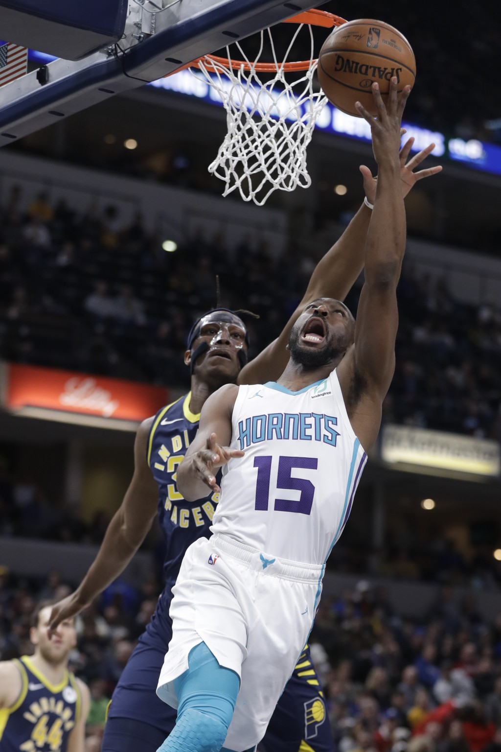 Charlotte Hornets' Kemba Walker, right, puts up a shot against Indiana Pacers' Myles Turner, left, during the first half of an NBA basketball game, Mo...