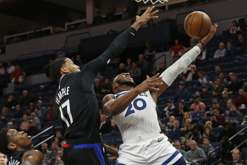 Minnesota Timberwolves' Josh Okogie, right, lays up as Los Angeles Clippers' Garrett Temple defends in the first half of an NBA basketball game Monday...