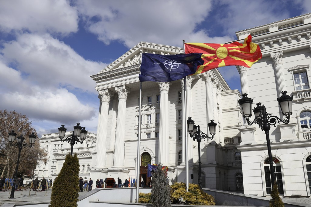 Macedonian, right, and NATO flag wave in front of the government building during a ceremony in Skopje, Tuesday, Feb. 12, 2019. Macedonian authorities ...