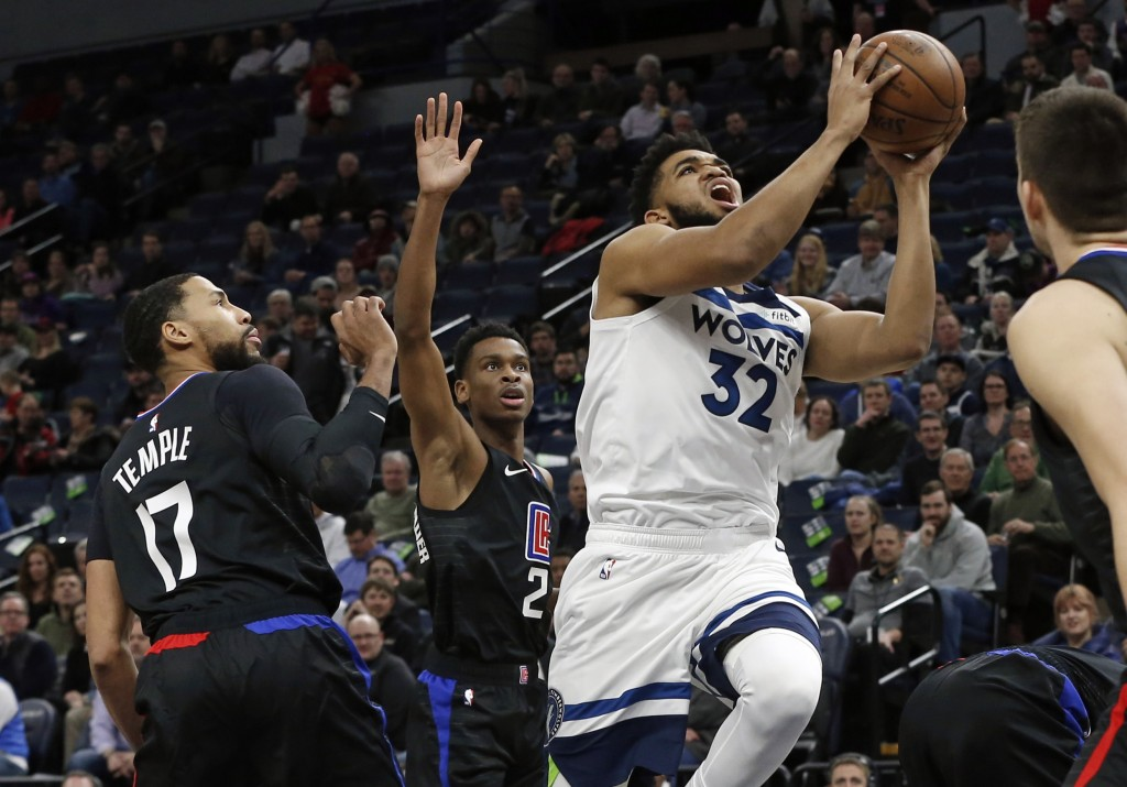 Minnesota Timberwolves' Karl-Anthony Towns, right, lays up as Los Angeles Clippers' Garrett Temple watches in the first half of an NBA basketball game...