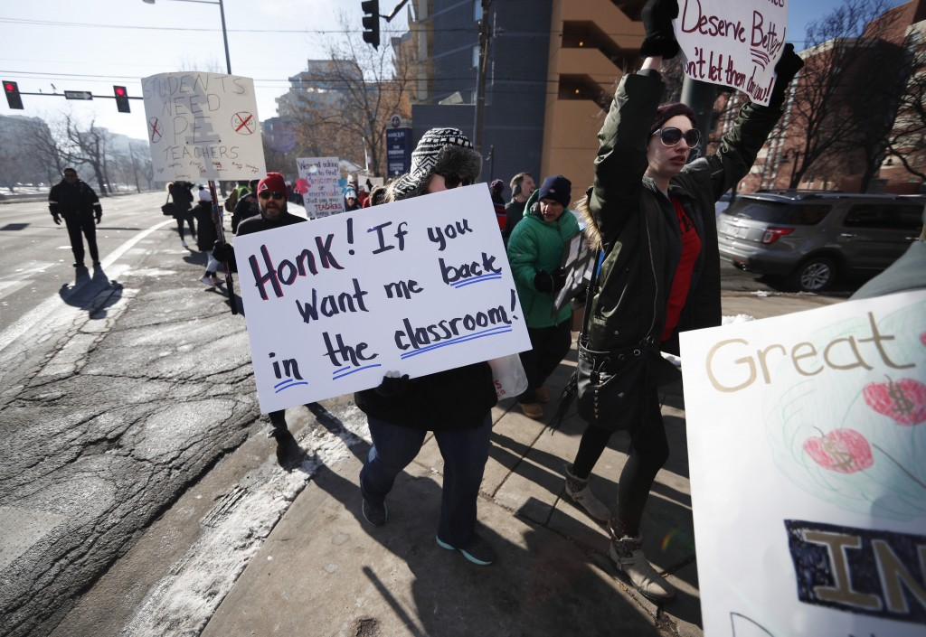 Teachers carry placards as they march along Speer Boulevard from West High School Monday, Feb. 11, 2019, in Denver. Denver teachers went on strike Mon...