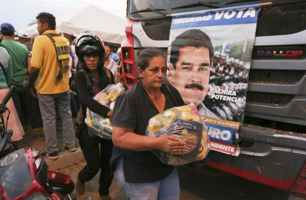 People carry bags with food provided by the Nicolas Maduro's government near the international bridge of Tienditas on the outskirts of Urena, Venezuel...