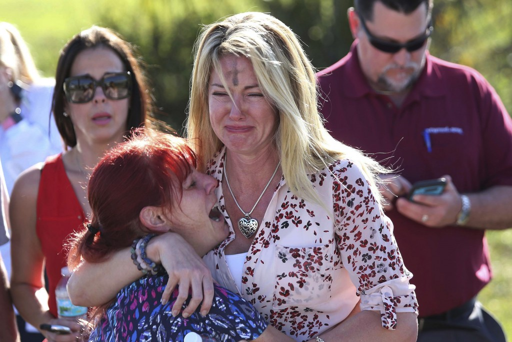 FILE - In this Feb. 14, 2018, file photo, Mechelle Boyle, right, embraces Cathi Rush as they wait for news after reports of a shooting at Marjory Ston...