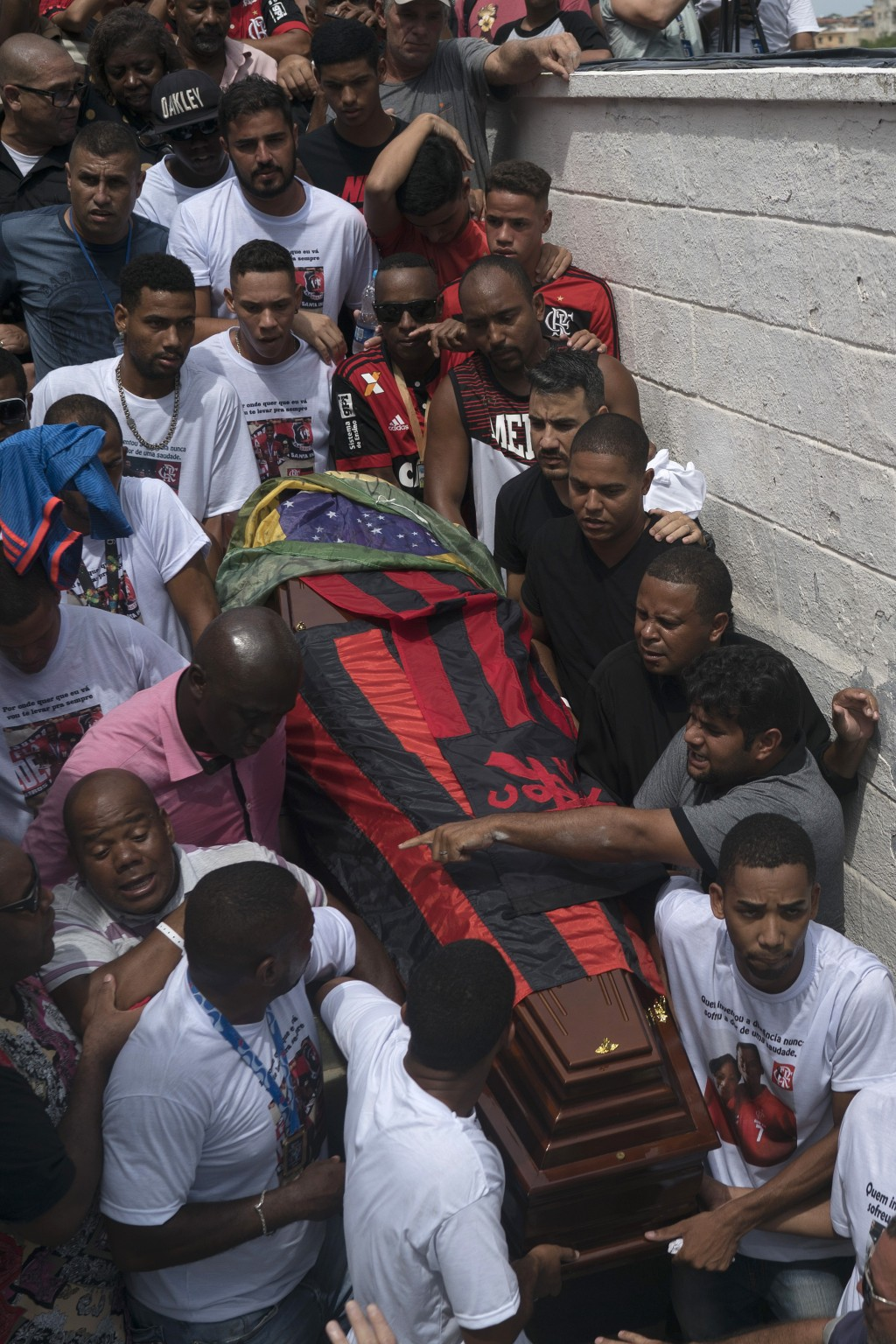 Friends and relatives carry the coffin that contain the remains of Samuel de Souza Rosa, one of the 10 young soccer players killed in a fire at the tr