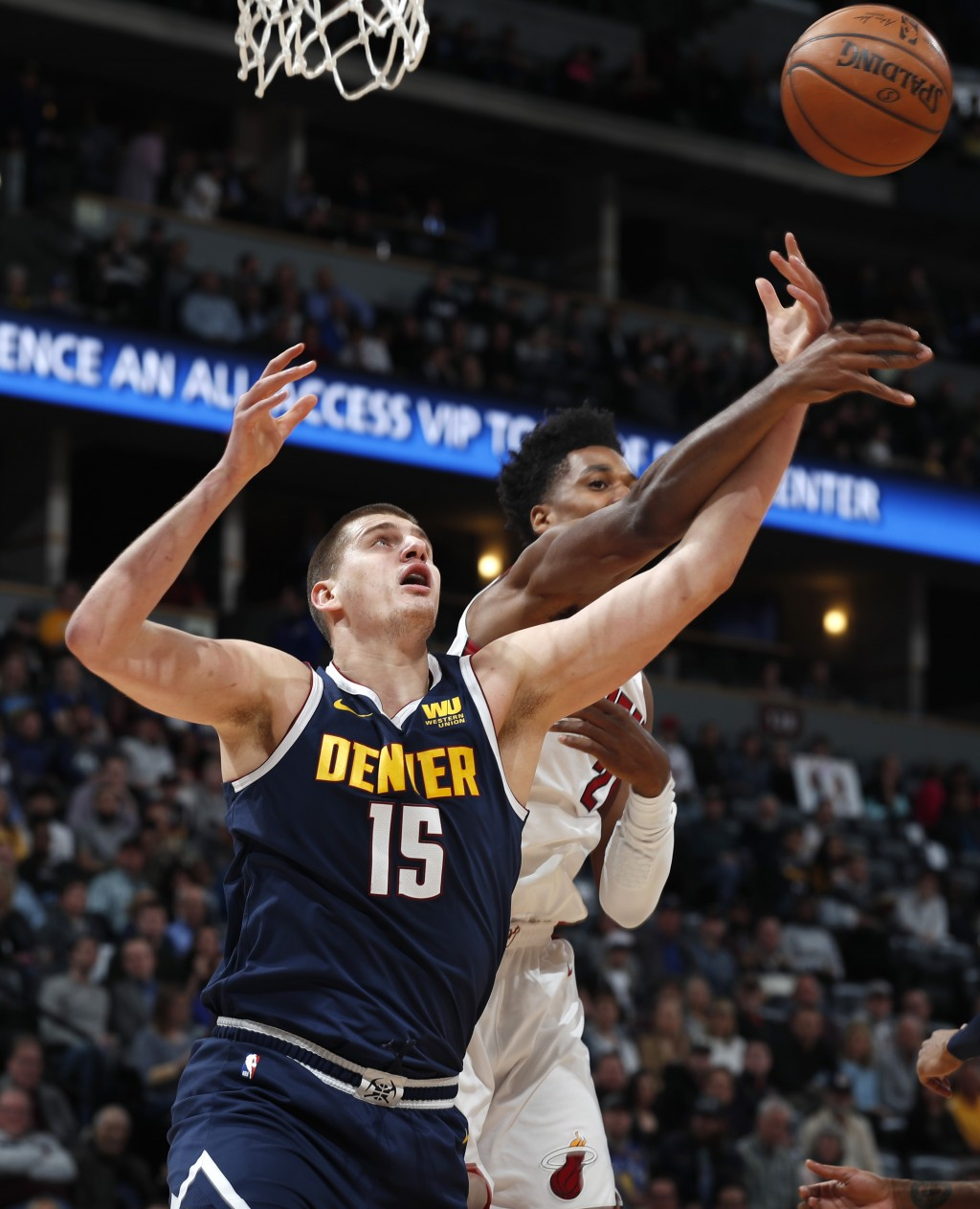Denver Nuggets center Nikola Jokic, left, fights for control of a rebound with Miami Heat center Hassan Whiteside, right, in the first half of an NBA