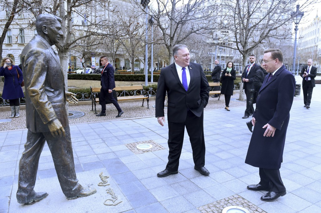 US Secretary of State, Mike Pompeo, center, is pictured next to a scuplture of former US President Ronald Reagan at the Liberty square (Szabadsag) in
