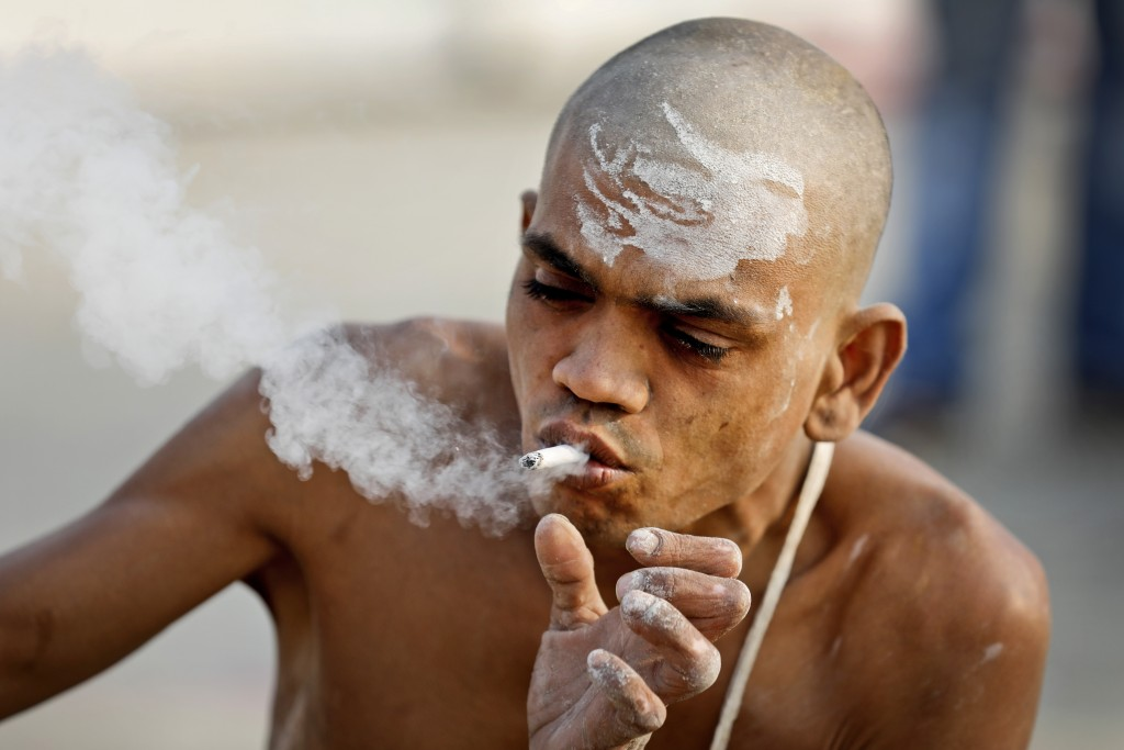 In this Jan. 27, 2019, photo, a Hindu holy man smokes a cigarette after a ritual for becoming Naga Sadhus or naked holy men at Sangam, the confluence ...