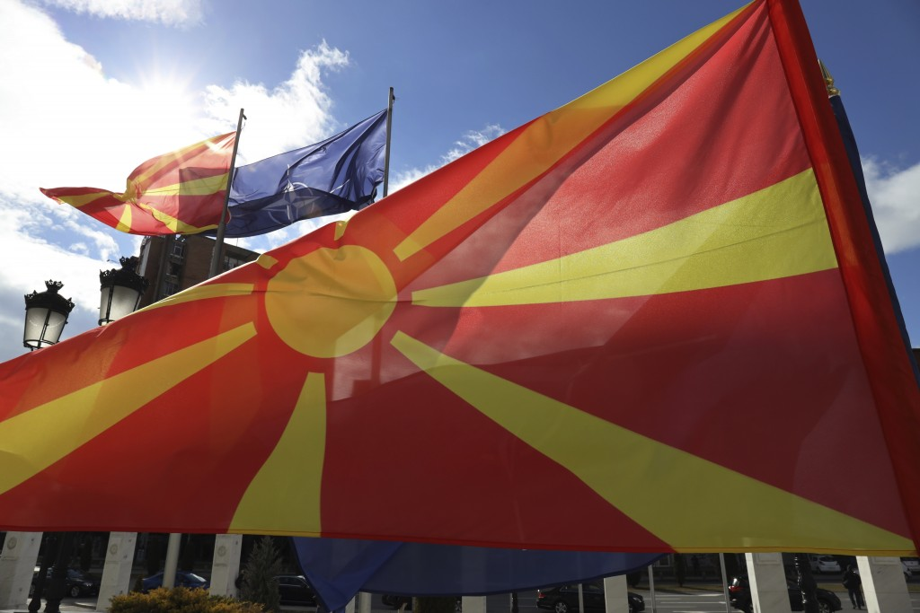 Macedonian and NATO flag wave in front of the government building during a ceremony in Skopje, Tuesday, Feb. 12, 2019. Macedonian authorities began re...