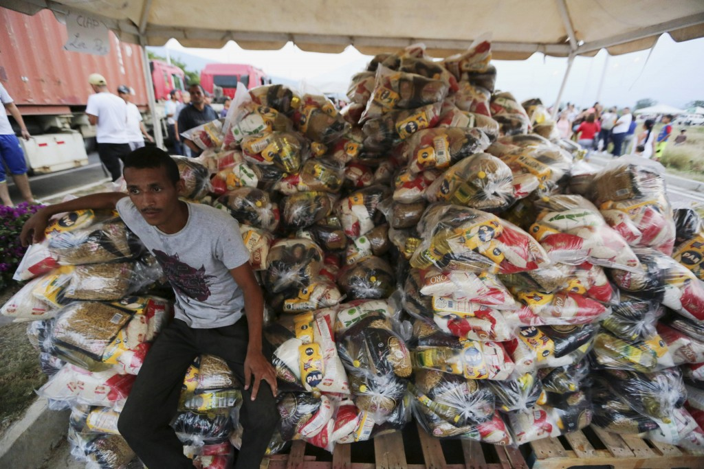 A volunteer takes a break during the distribution of bags with food subsidized by the Nicolas Maduro's government near the international bridge of Tie