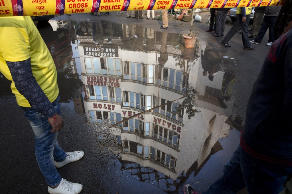 In this Tuesday, Feb. 12, 2019, file photo, The Arpit Palace Hotel is reflected in a puddle after an early morning fire at the hotel killed more than ...