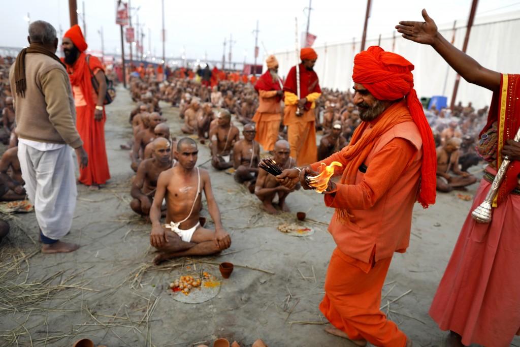 In this Jan. 27, 2019, photo, Hindu men perform prayers for becoming Naga Sadhus or naked holy men at Sangam, the confluence of three holy rivers duri...