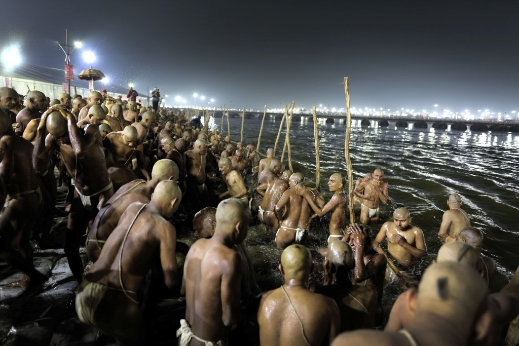 In this Jan. 27, 2019, photo, Hindu men take dip for becoming Naga Sadhus or naked holy men at Sangam, the confluence of three holy rivers during the