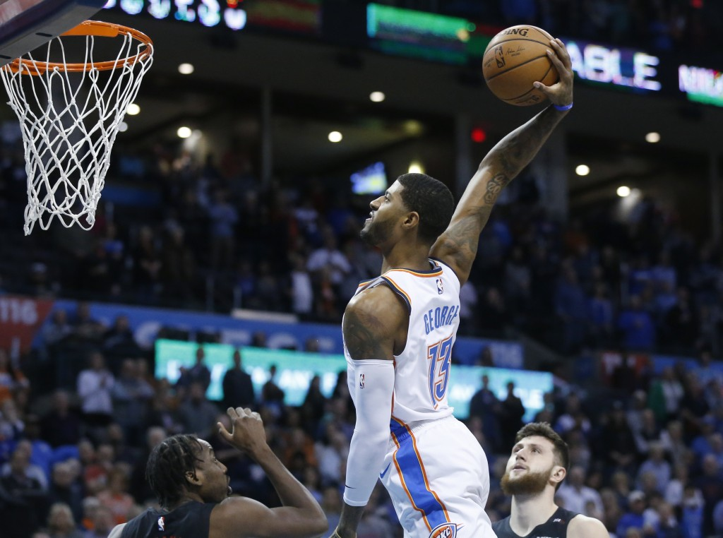 Oklahoma City Thunder forward Paul George (13) goes up for a dunk between Portland Trail Blazers forward Al-Farouq Aminu, left, and center Jusuf Nurki