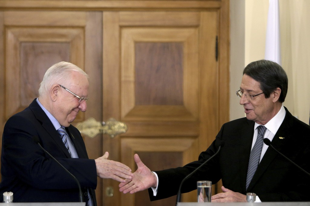 Cyprus' President Nicos Anastasiades, right, shakes hands with Israel's President Reuven Rivlin after their meeting at the presidential palace in divi