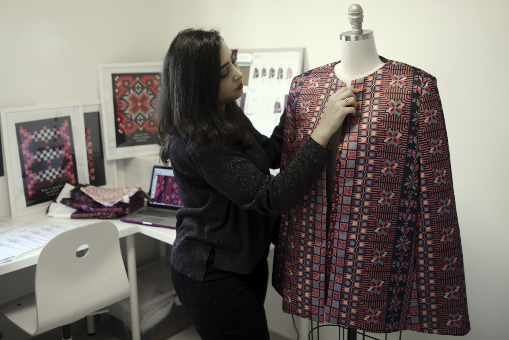 In this Tuesday, Jan. 29, 2019 photo, designer Natalie Tahhan works on a modern version of the traditional Palestinian thobe in her studio in east Jer...