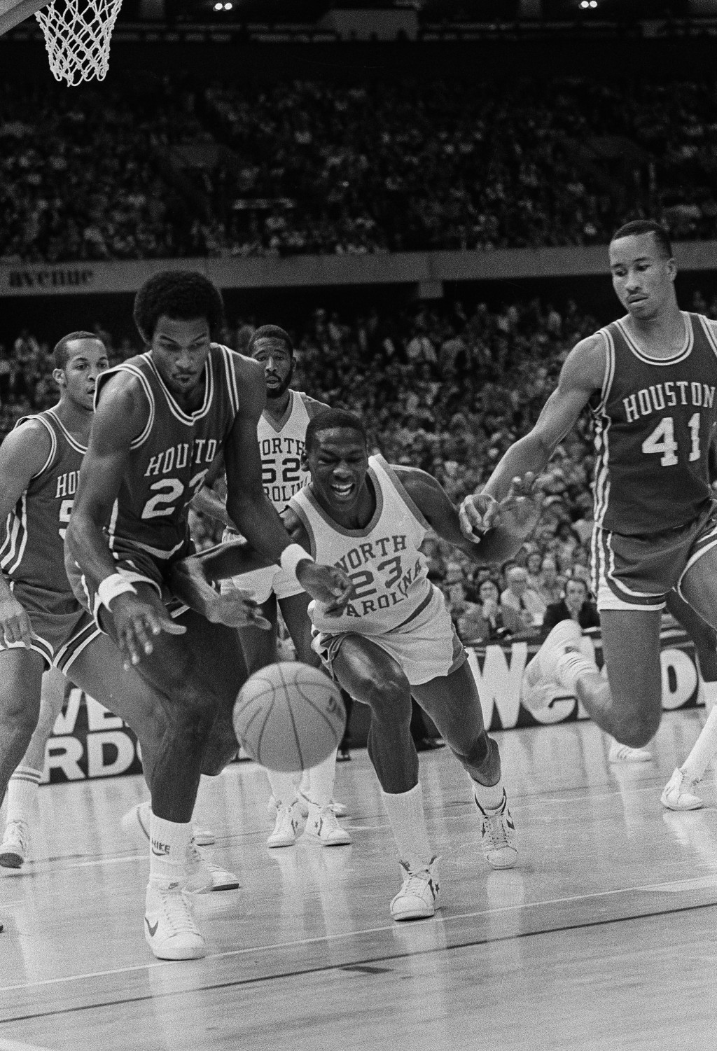 File- This March 29, 1982, file photo shows Houston's Clyde Drexler, left, and North Carolina's Michael Jordan, center, battling for the ball  during ...