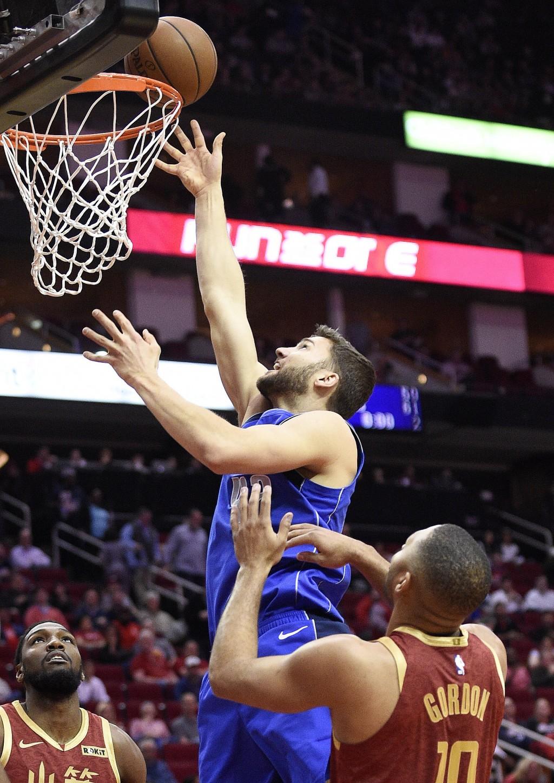 Dallas Mavericks forward Maximilian Kleber, left, shoots over Houston Rockets guard Eric Gordon during the first half of an NBA basketball game, Monda...