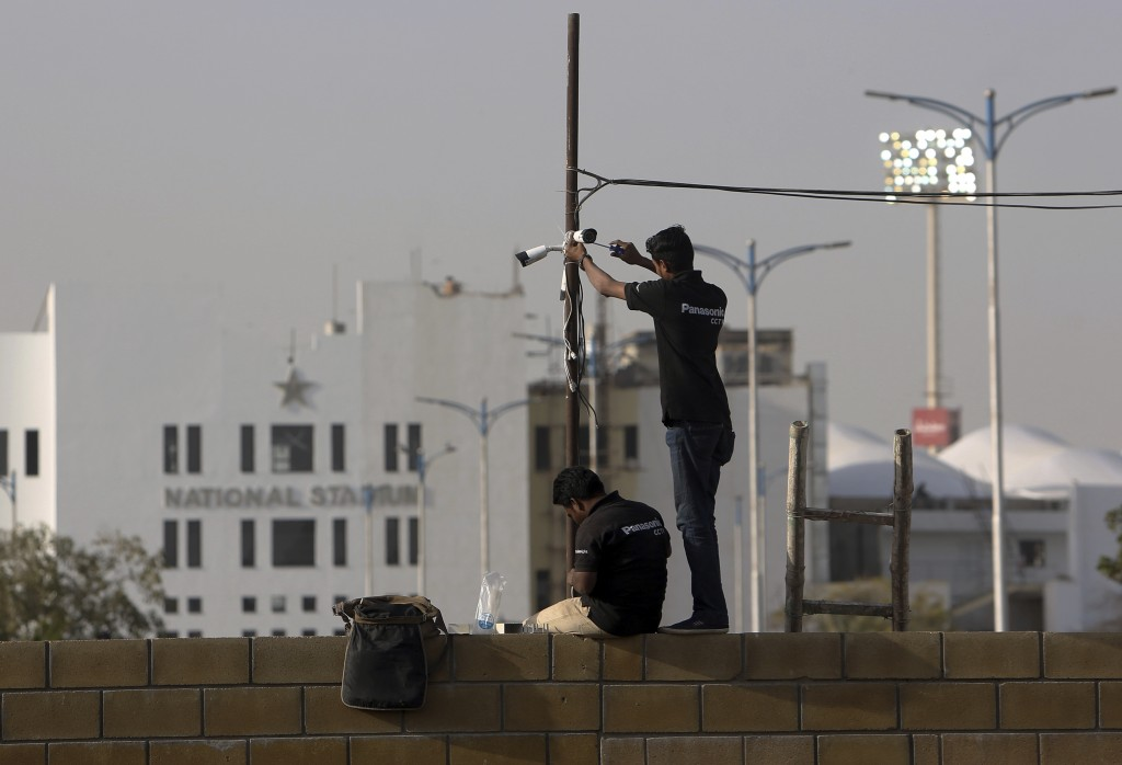 In this Feb. 9, 2019, photo, Pakistani technician fix security cameras at National Stadium ahead of upcoming Pakistan Super League in Karachi, Pakista