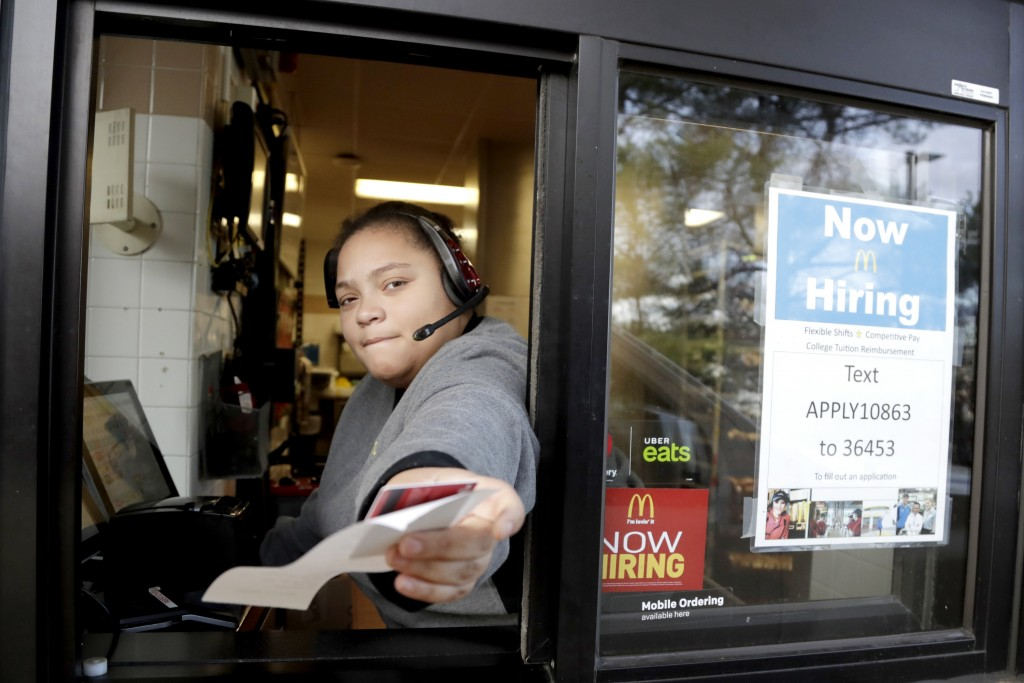 FILE- In this Jan. 3, 2019, file photo a cashier returns a credit card and a receipt at a McDonald's window, where signage for job openings are displa