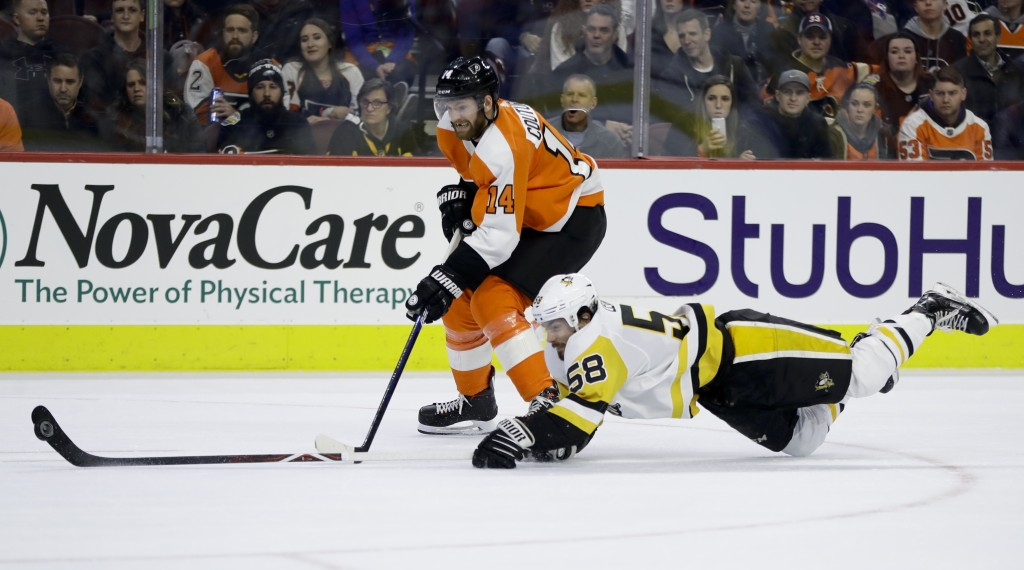 Pittsburgh Penguins' Kris Letang (58) dives to keep the puck away from Philadelphia Flyers' Sean Couturier (14) during the second period of an NHL hoc
