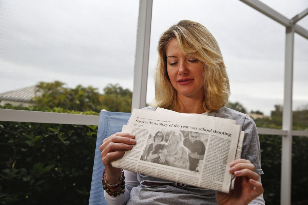 In this Jan. 30, 2019, photo, Mechelle Boyle holds a newspaper with an iconic photo from the school shooting showing her embracing Cathi Rush as she s...