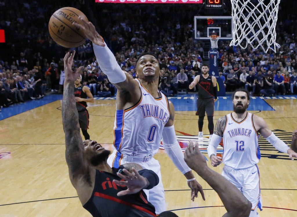 Oklahoma City Thunder guard Russell Westbrook (0) blocks a shot by Portland Trail Blazers guard Damian Lillard, left, in the first half of an NBA bask...