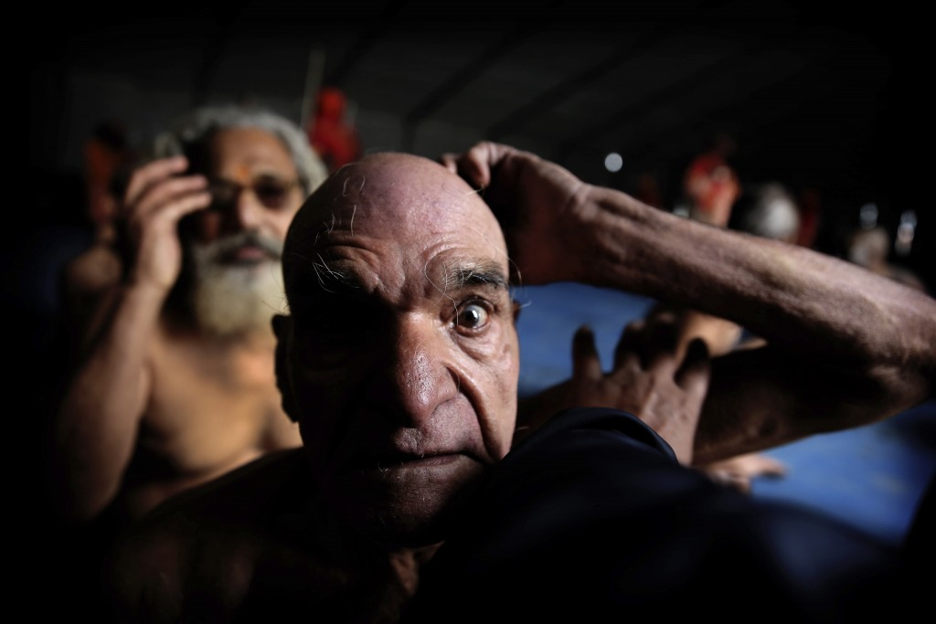 In this Jan. 27, 2019, photo, Hindu men get their hair cut in a ritual before becoming Naga Sadhus or naked holy men at Sangam, the confluence of thre