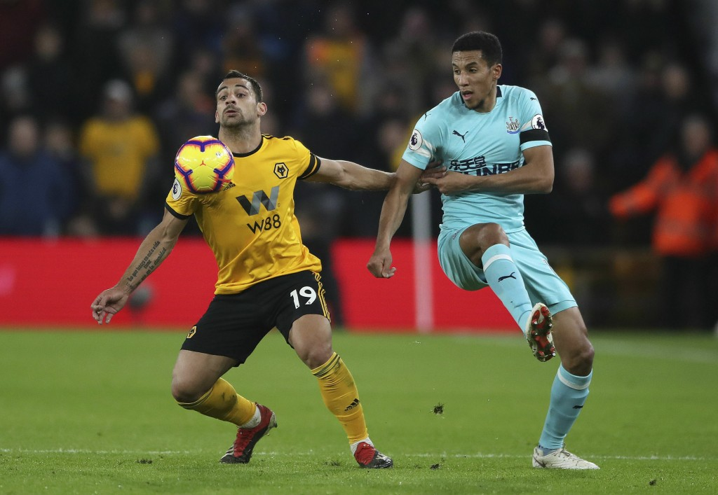 Wolverhampton Wanderers' Jonny Castro, left and Newcastle United's Isaac Hayden battle for the ball, during the English Premier League soccer match be...