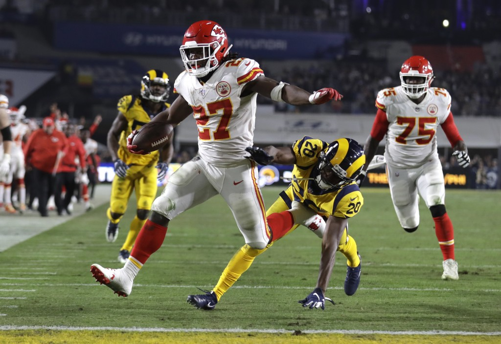 FILE - In this Nov. 19, 2018, file photo, Kansas City Chiefs running back Kareem Hunt (27) scores a touchdown ahead of Los Angeles Rams free safety La