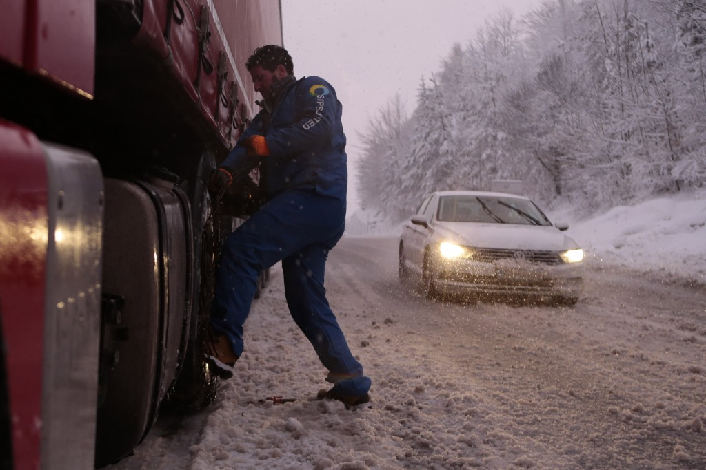 Bosnian truck driver checks tyres on the truck during a snow storm on a road near Sarajevo, Bosnia, Monday, Feb. 11, 2019. Heavy snow has descended on...