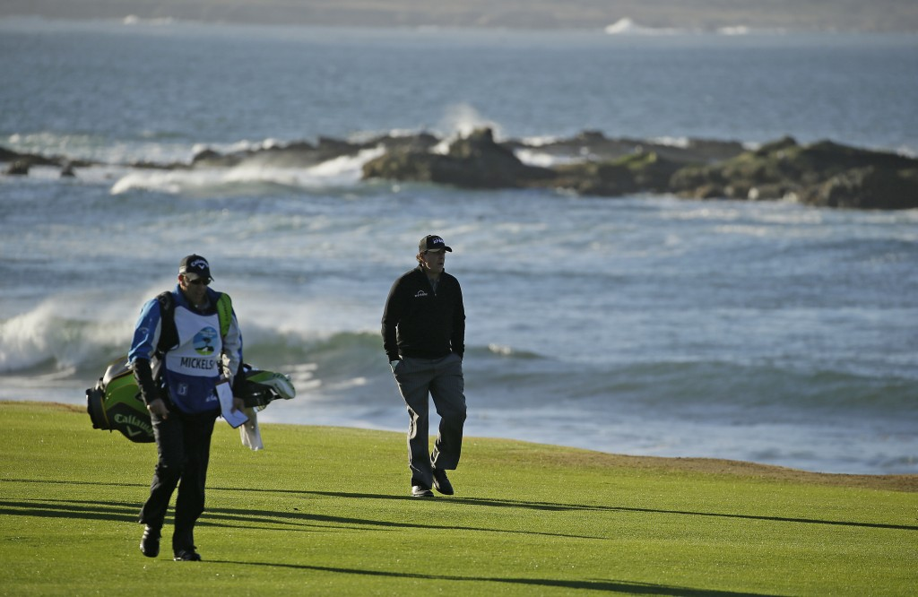 Phil Mickelson walks up the 18th fairway of the Pebble Beach Golf Links with his brother and caddie Tim Mickelson during the final round of the AT&T P