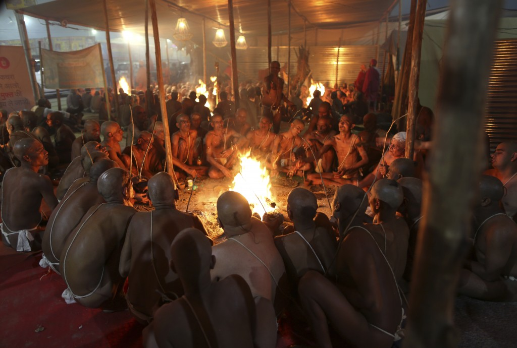 In this Feb. 7, 2019 photo, Hindu holy men perform prayers for becoming Naga Sadhus or naked holy men at Sangam, the confluence of three holy rivers d...