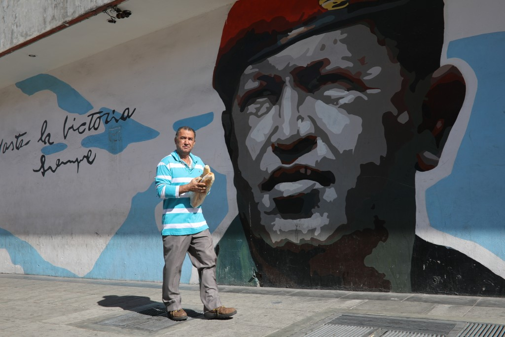 A man walks with a couple loaves of bread past a mural of Venezuela's late former president Hugo Chavez, in Caracas, Venezuela, Tuesday, Feb. 12, 2019